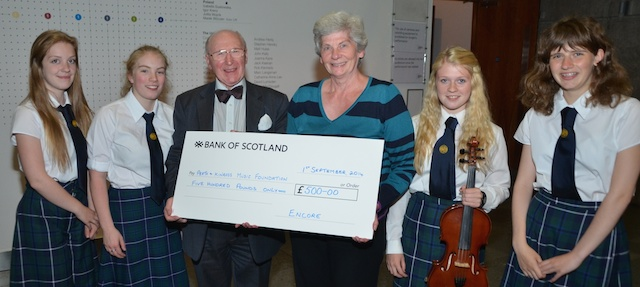 Perth Youth Orchestra members (L–R) Sarah Adam, Katriona Allen,  Sophie Moyes and Louise Brown watch as Henry Neil accepts a cheque for £500 from Encore's Lynda Piper.